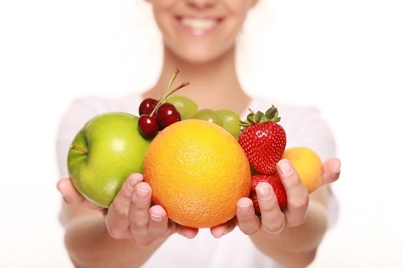 Una donna con frutta e verdura come prevenzione del cancro al seno